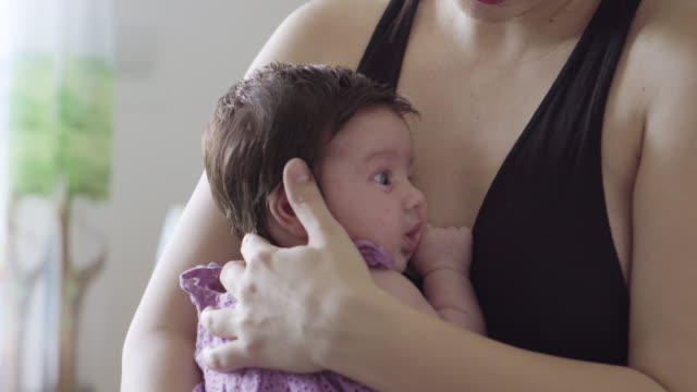 mother rocking baby at home - dondolarsi video stock e b–roll