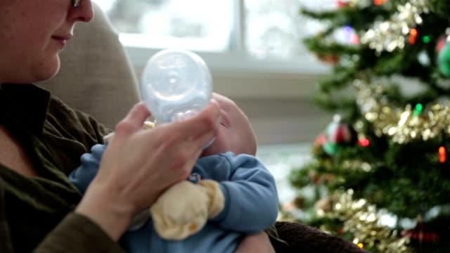 vídeos y material grabado en eventos de stock de madre mecer su recién nacido cerca de árbol de navidad y tormenta de nieve - balancearse