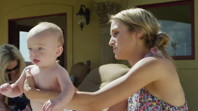 SLO MO MS TU Mother rubbing suntan lotion on baby son's (6-11 months) back, sitting on patio / Cedar Hills, Utah, USA