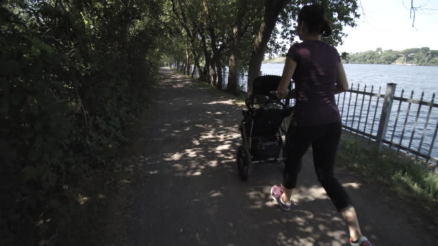 mother running walking with baby stroller in park - three wheeled pushchair stock videos & royalty-free footage
