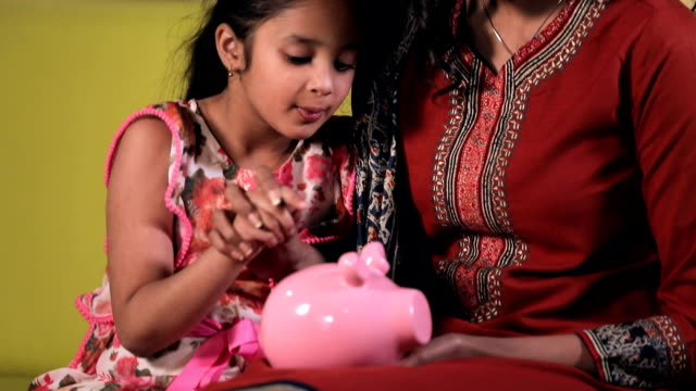 mother saving indian coin with her daughter into piggy bank, delhi, india - piggy bank stock videos & royalty-free footage