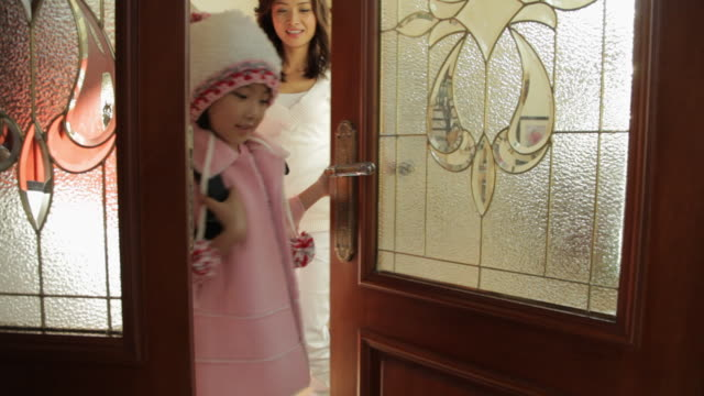 vídeos de stock e filmes b-roll de ms mother saying goodbye to daughter going off to school at doorway / china - família com um filho