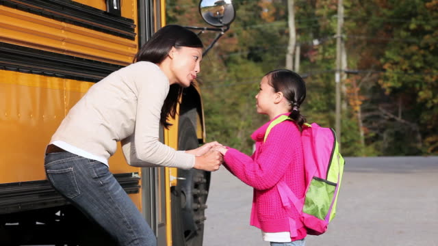 MS Mother saying goodbye to young daughter next to school bus / Richmond, Virginia, United States
