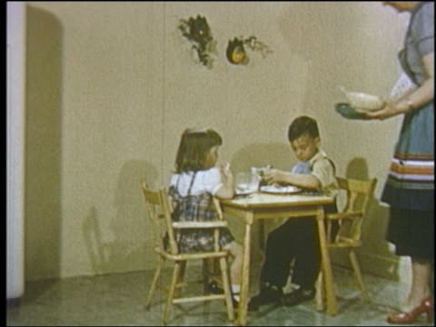 1952 mother serving 2 young children sitting at kiddie table - 1952 stock videos & royalty-free footage
