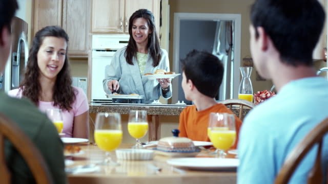 ms mother serving breakfast in kitchen / renton, washington, usa  - orange juice stock videos & royalty-free footage