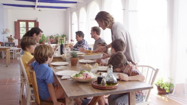 mother serving food to children at dining table - dining room stock videos & royalty-free footage