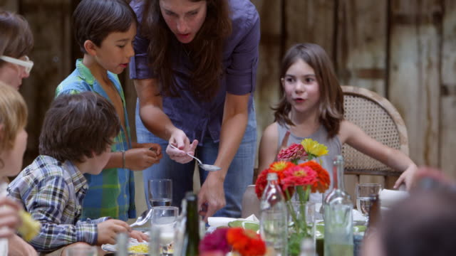 ms mother serving food to children dining at banquet table during dinner party in rustic building - feinschmecker essen stock-videos und b-roll-filmmaterial
