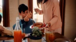 Mother serving pancakes with strawberries to son as breakfast