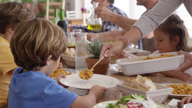 mother serving pasta to children at dining table - pasta video stock e b–roll