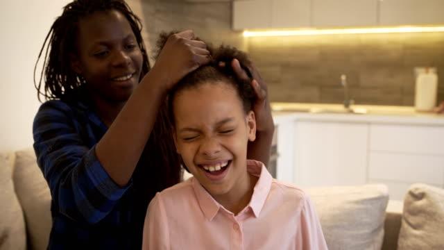 vídeos de stock, filmes e b-roll de mãe define o penteado da filha. conceito da matriz e da filha - cabelo encaracolado