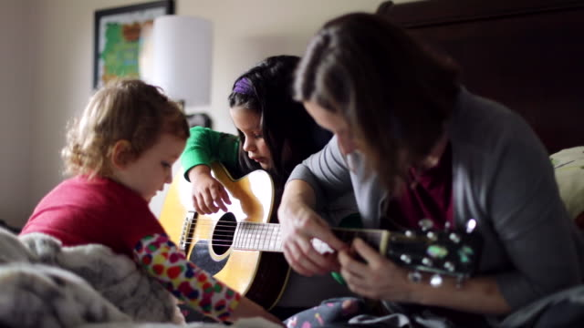 vídeos de stock e filmes b-roll de mother showing daughters how to play guitar - artista