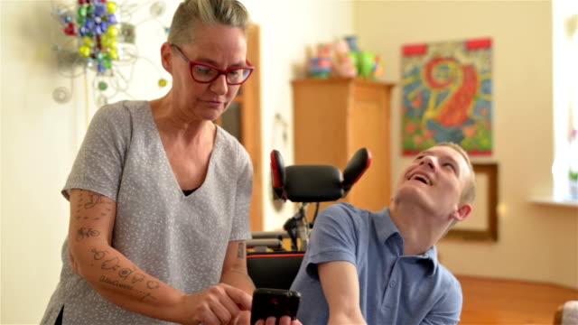 Mother showing funny videos to disabled son