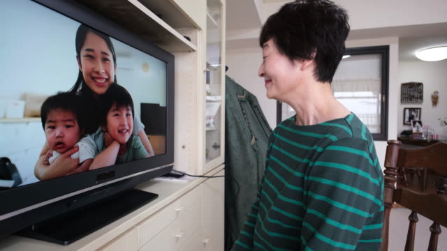 mother showing her children to senior mother on video call - remote location stock videos & royalty-free footage