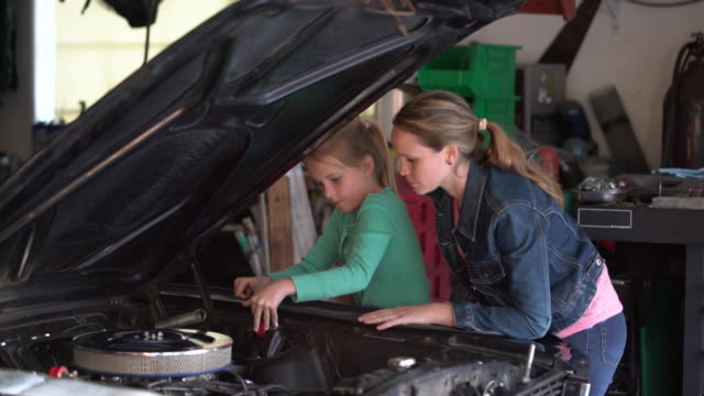 MS Mother showing her daughter how to fix a car engine.
