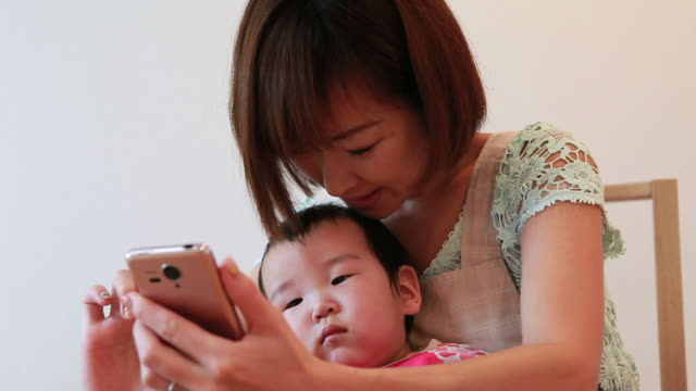 MS Mother showing smart phone to baby  / Minato-ku,  Tokyo,  Japan