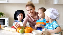 Mother shows children how to cook. Girl looking a recipe on a mobile phone