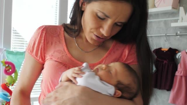vidéos et rushes de mère chantant une berceuse pour son bébé nouveau-né - famille avec un enfant