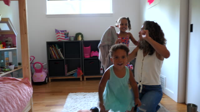 ms mother singing and playing with dancing daughters in bedroom - family with two children stock videos & royalty-free footage
