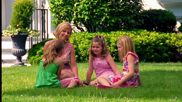 A mother sits in the grass, talking with her three daughters.