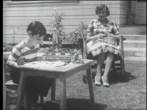 b/w 1952 mother sits knitting while son finger paints outdoors - 1952 stock videos & royalty-free footage