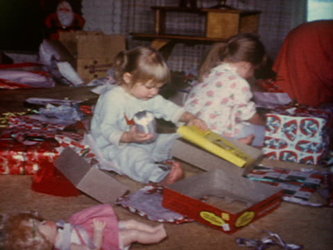 a mother sits with her daughters as they open christmas presents. - home movie stock videos & royalty-free footage