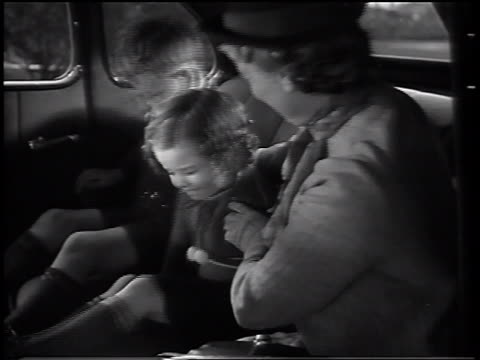 B/W 1937 mother sitting in backseat with small son + daughter bouncing on seat / commercial