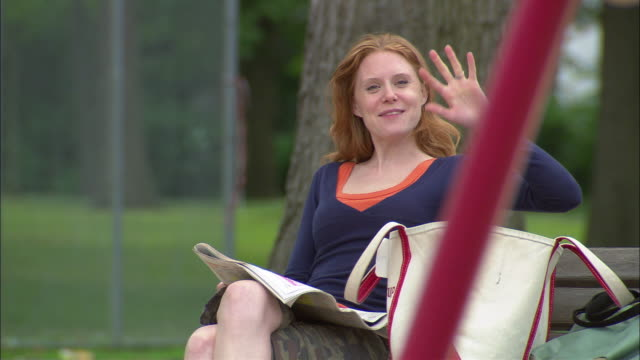 selective focus cu mother sitting in park reading paper and waving to someone before urging child on swing to be careful/ fanwood, new jersey - kinderspielplatz stock-videos und b-roll-filmmaterial