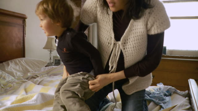 MS Mother sitting on bed and putting trousers on son (2-3) / New York City, New York, USA