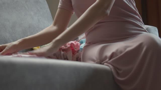 ソファに座って赤ちゃんの服を折りたたむ母親 - たたむ点の映像素材/bロール
