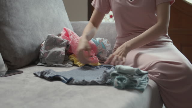 mother sitting on sofa and folding the baby clothes - folded stock videos & royalty-free footage