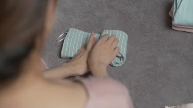 ソファに座って赤ちゃんの服を折りたたむ母親 - 家事点の映像素材/bロール