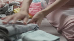 Mother sitting on sofa and folding the baby clothes