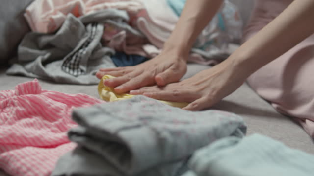 mother sitting on sofa and folding the baby clothes - washing stock videos & royalty-free footage