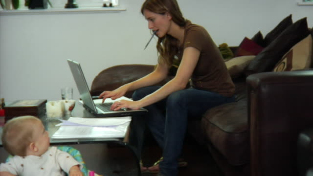 SLO MO WS Mother sitting on sofa and using laptop, baby boy (6-11 months) in foreground / London, United Kingdom