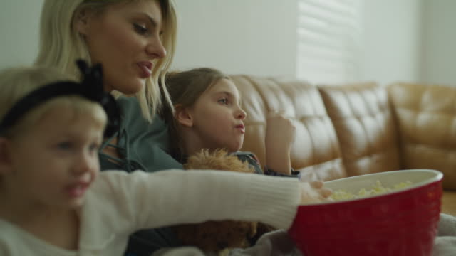 vídeos y material grabado en eventos de stock de mother sitting on sofa with daughters and dog eating popcorn and watching television / vineyard, utah, united states - animal family