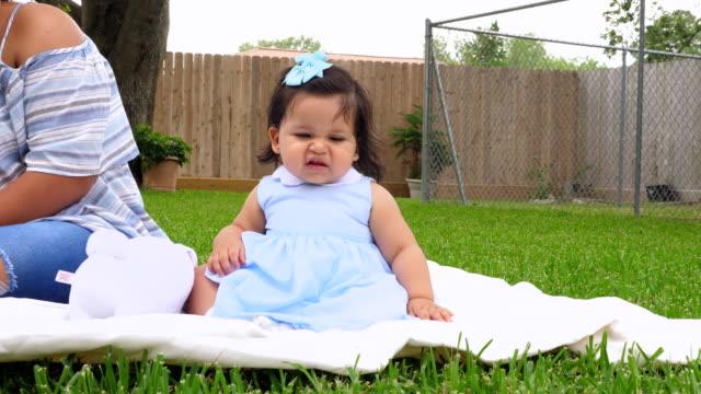 vidéos et rushes de ms mother sitting with infant daughter on blanket in backyard - curiosité