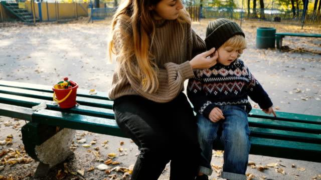 Madre sentada con hijo en la banca en el parque en otoño