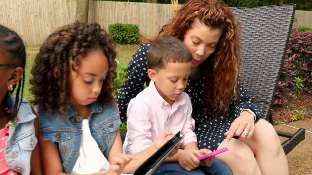 ms zi zo mother sitting with young kids playing game on digital tablet during backyard party - family with three children stock videos & royalty-free footage