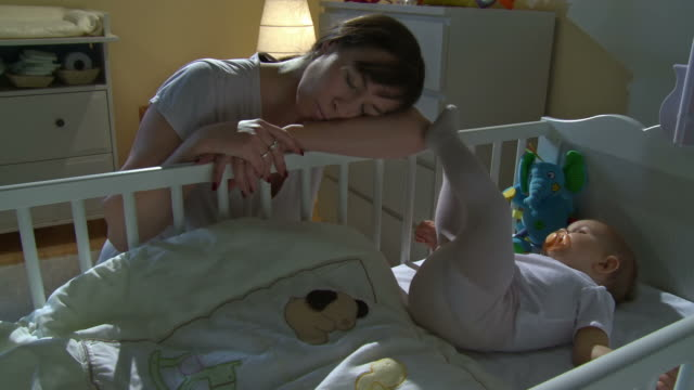 stockvideo's en b-roll-footage met hd crane: mother sleeping beside sleepless baby - wakker worden