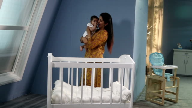 mother sleeping her baby in cot, delhi, india - babygro stock videos & royalty-free footage