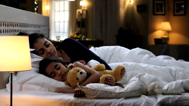 mother sleeping with her daughter in the home, delhi, india - ora di andare a letto video stock e b–roll