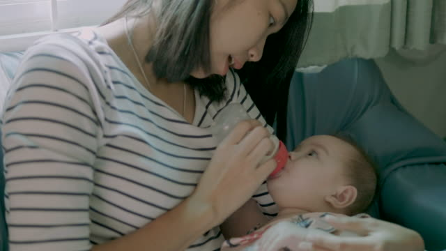 mother smiles as she feeds her baby milk from a bottle. - east asian ethnicity stock videos & royalty-free footage
