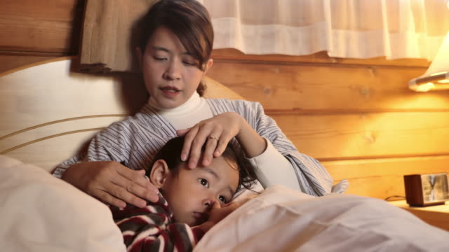 mother snuggling her son. staying home on a sick day - frustration asian failure stock videos & royalty-free footage