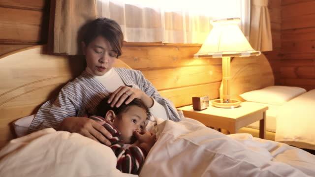 母は息子を寄り添う。病気の日に家にいる - 憂鬱点の映像素材/bロール