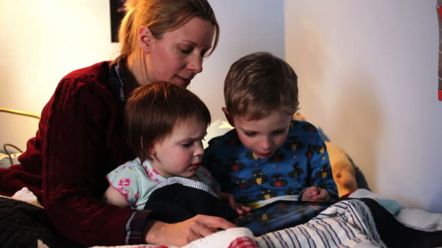 mother, son and daughter looking to digital tablet - greater london stock videos & royalty-free footage