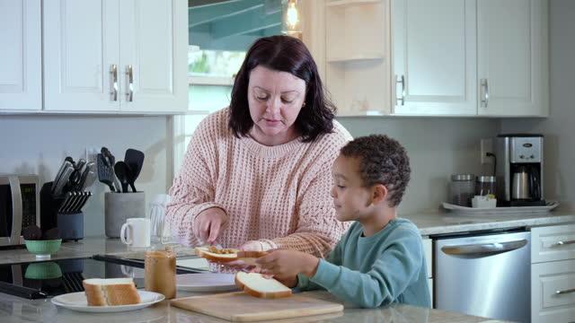 vidéos et rushes de mère, fils faisant le sandwich de beurre d'arachide dans la cuisine - sandwich