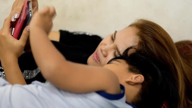 vidéos et rushes de mère fils sommeil jeu smartphone. - doigt humain