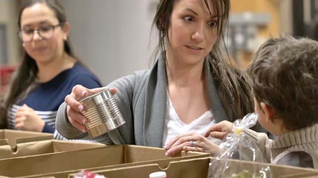madre & figlio che si offrono volontari in una banca del cibo - assistenza ai bisognosi video stock e b–roll