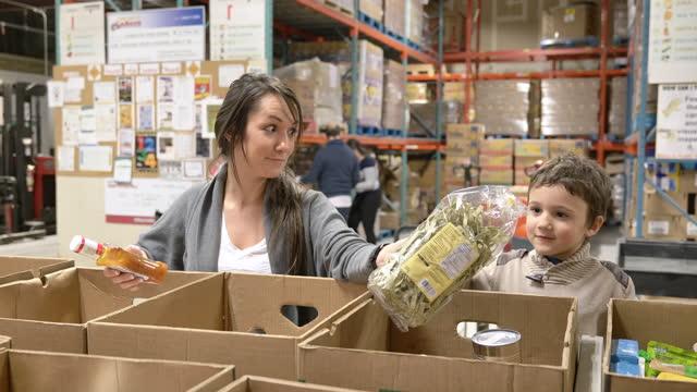mother & son volunteering at a food bank - volunteer stock videos & royalty-free footage