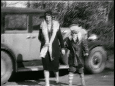 b/w 1925 mother + son walking from car towards camera outdoors / home movie - 1925 stock videos & royalty-free footage